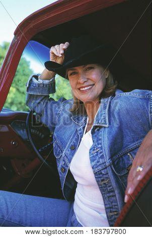 Woman wearing cowboy hat in truck