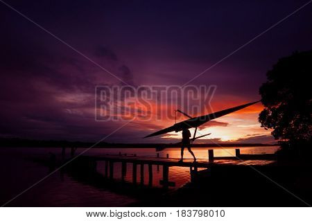 Rower silhouette during sunrise on a lake