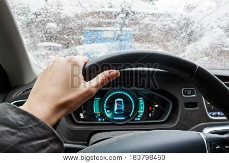 Close up woman hand on black steering wheel driving