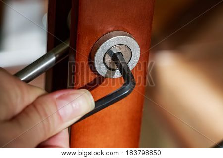 Close up hand holding metal hexagon key in hole in furniture