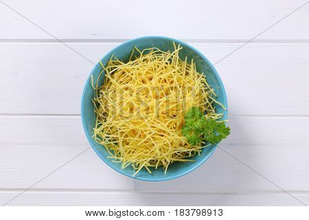 bowl of dry soup noodles on white wooden background
