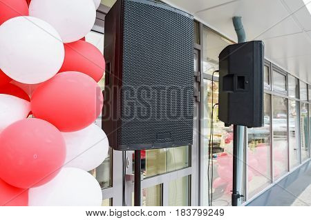 Close up two black loudspeakers hanging outside a supermarket with red and white baloons in foreground