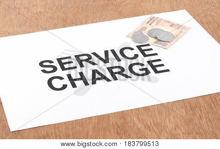 Service charge or tips concept indicated by text and Indian currency coins and ten rupees.
