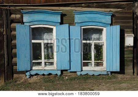 The window with the wooden carved architrave in the old wooden house in the old Russian town. Irkutsk