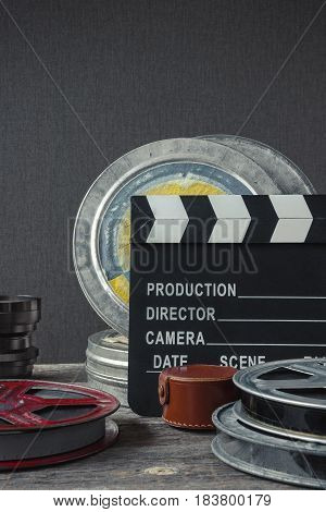 Clapperboard tin boxes with film and lens stand on a wooden table.