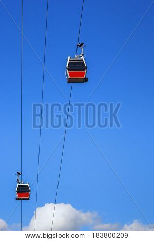 Two cable car cabins lifted on a sunny day against the blue sky