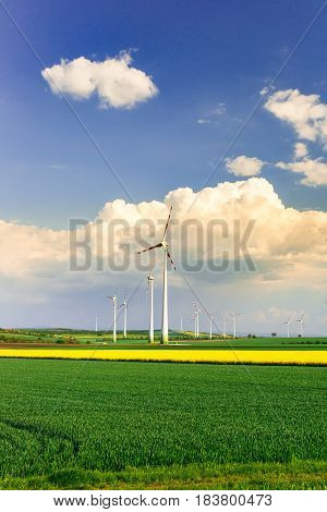 Wind farm with spinning wind turbines amidst agricultural land of intensive crop production. Sustainable and renewable power production ecology and environmental conservation concept.