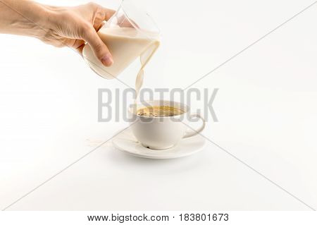 Close-up Partial View Of Hand Pouring Milk Into Coffee Isolated On White