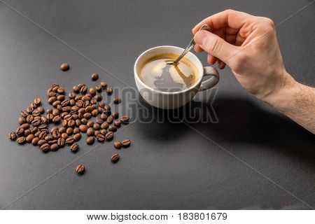 Close-up Partial View Of Person Mixing Hot Coffee With Spoon