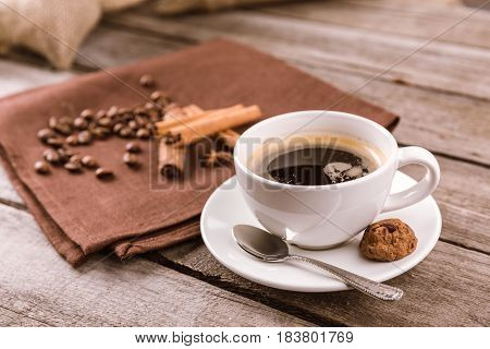 Side View Of Coffee Mug Steam And Cinnamon Sticks On Napkin