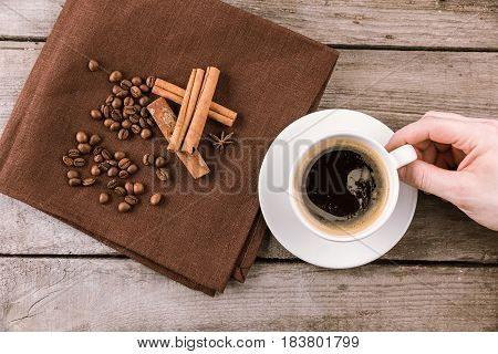 Top View Of Hand Holding Coffee Mug Steam On Wooden Tabletop