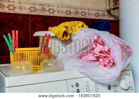 Close up top of modern washing machine in bathroom with facilities on it: cleanser, washing basin with colorful clothes in it, colorful plastic containers and pegs