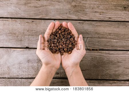 Partial View Of Coffee Beans In Hands On Wooden Tabletop