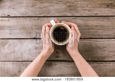 Partial View Of Coffee Mug Steam In Hands On Wooden Tabletop