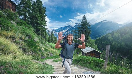 adult hiker in the Apls mountains. Trek near Matterhorn mount. a man with a happy face on the trail on the alpine meadows with rural houses