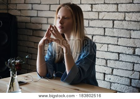 Blond Girl Is Sitting With Headphones And Looking Thoughtfully Into The Distance, Combining In Front