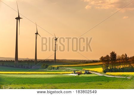 Wind farm with spinning wind turbines and tractor spraying pesticides in the foreground. Sustainable and renewable power production agriculture and environmental conservation concept.