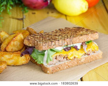 Sandwich of fresh tuna salad and melted cheddar cheese.