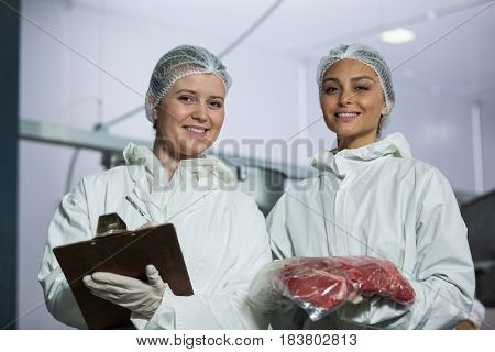 Portrait of female butchers maintaining records on clipboard at meat factory