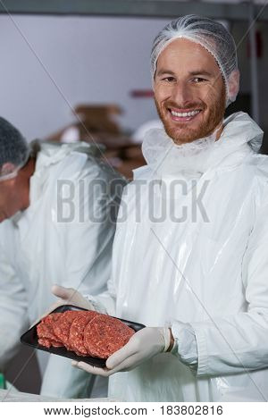 Butcher holding raw meat patties arranged in tray at meat factory