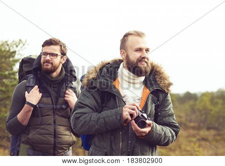 Two bearded men hiking in swamps and taking pictures. Camp, adventure, trip and traveling concept.
