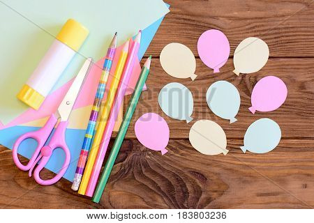 Creating a paper card with balloons. Step. Guide for kids. Air day or birthday card idea. Balloons from paper, scissors, glue stick, colored paper, pencils on a table. Art activity for kids. Top view