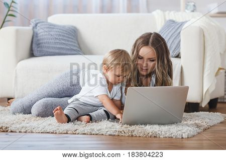 cheerful little boy and his mother lying on the floor at home while playing game on the laptop