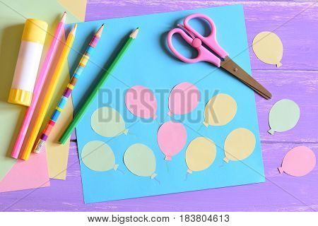 Paper card with air balloons, scissors, glue stick, paper air balloons, colored paper, pencils on a table. Air day or birthday card. Fun art activity for preschool and kindergarten. Easy kids crafts