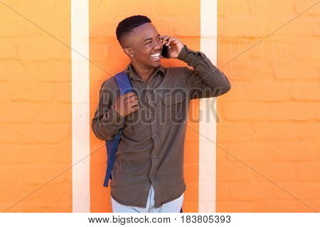 Happy Young Black Guy Talking On Mobile Pone By Orange Wall
