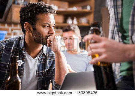 Serious Young Man Using Laptop While Young People Having Fun With Beer