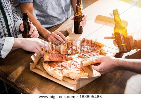 Close-up Partial View Of Young People Having Fun With  Beer And Pizza