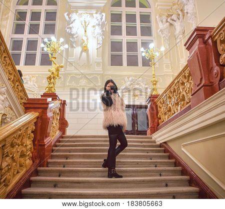 Happy trendy girl making photo with retro camera on strairs in luxury interior