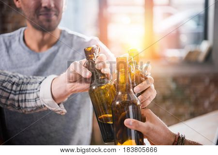 Close-up View Of Young People Having Fun And Clinking Beer Bottles