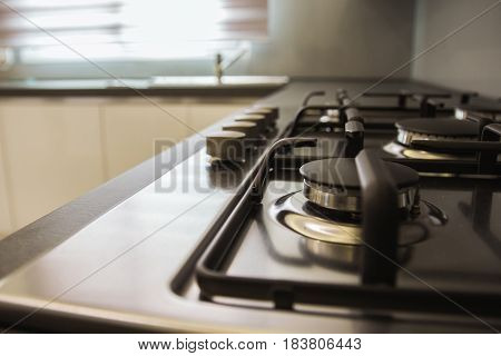 Kitchen Cooker Hob with light streaming in from a window and a kitchen sink in the background.