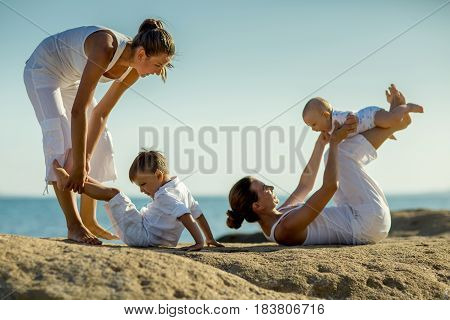 Mothers and their sons are doing yoga exercises at the seashore of Mediterranean sea