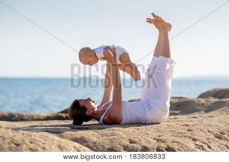 A Mother And A Son Are Doing Yoga Exercises At The Seashore Of Mediterranean Sea