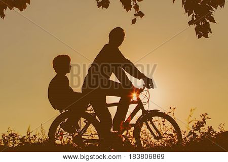 father with son riding bike in sunset nature