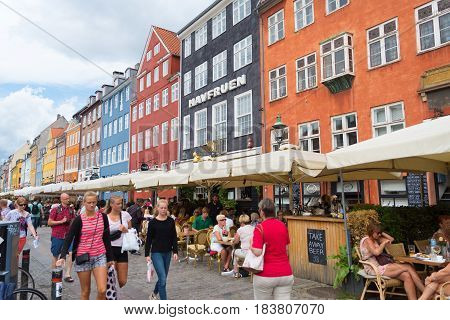 COPENHAGEN DENMARK - JULY 31 2016: Famous Nyhavn promenade with its colorful buildings. It is one of the most famous landmarks in the country