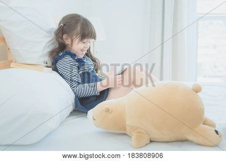 Cute Little Girl Enjoy Watching Cartoon On Smart Tablet With Cute Doll While Sitting On Bed In Kid B