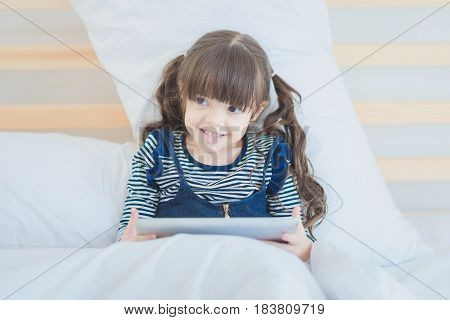 Cute Kid Girl Smiling While Using Digital Smart Tablet On Bed In Kid's Bedroom At Home.photo Design