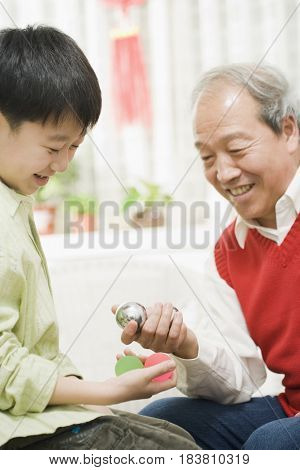Chinese grandfather and grandson holding balls