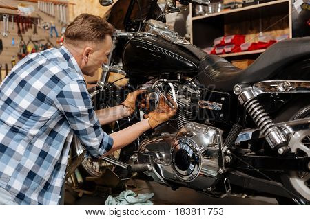 Make it tighter. Industrious to decent specialist tightening a bolt on his lovely vehicle while spending time at his workshop maintaining it
