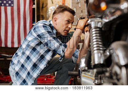 Attention to details. Attractive scrupulous master serviceman fulfilling a new order and repairing vintage motorbike while tightening a bolt