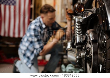Fixing all the bolts. Masculine mature scrupulous expert being focused while maintaining a bike and enjoying his work