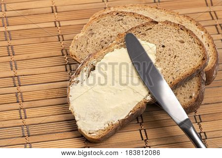 Close up a  knife spreading butter on bread