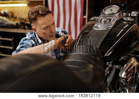 Making another checkup. Hardworking capable industrious man doing some final touches on the bike while repairing it and fulfilling clients order