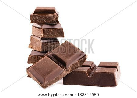 Chocolate cubes on heap pieces of bitter dark chocolate bar isolated on white background side view.