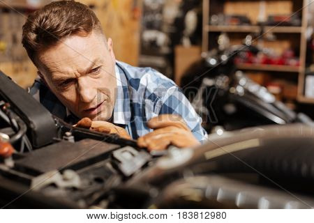 Lovely lines. Capable diligent hardworking man working on his gorgeous vintage vehicle by fixing all mechanisms and making it great again
