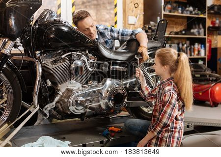 Best assistant. Enchanting lovely curios daughter and her dad enjoying their weekend while the dad fixing his motorbike and the daughter assisting him