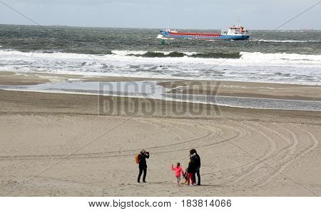 Vlieland. People walking on the beach of the island Vlieland on the background a freighter in the North Sea. The Netherlands.The N